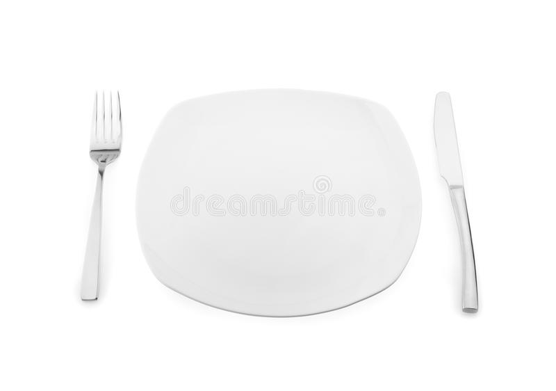 Empty plate, fork and knife on white background.  royalty free stock photography