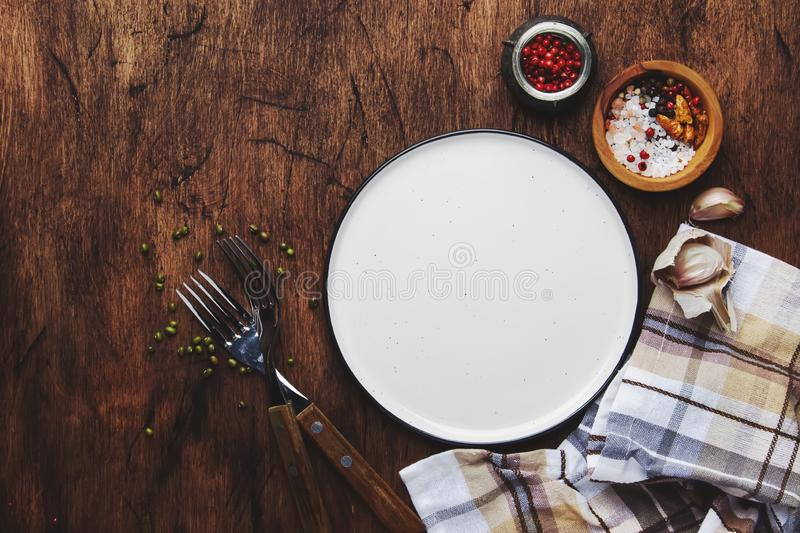 Empty plate with forks, napkin and spices on vintage wooden kitchen table, rustic setting, ready to serve, top view stock images