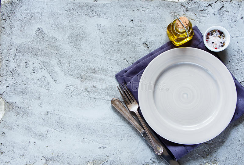 Empty plate, knife and fork. Simple food background with napkin, empty plate, knife and fork over concrete textured board, top view, copy space royalty free stock photo