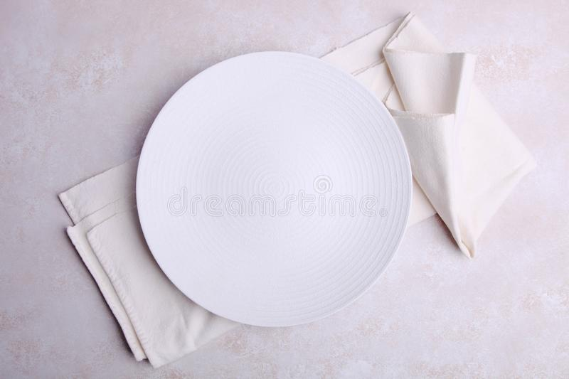 Empty plate on napkin. One clean round empty plate on napkin on neutral background. Concept dishes. Top view royalty free stock photos