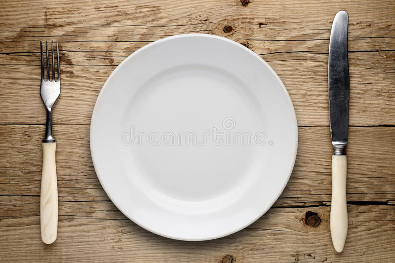 Empty plate, old fork and knife. On wooden background stock photography