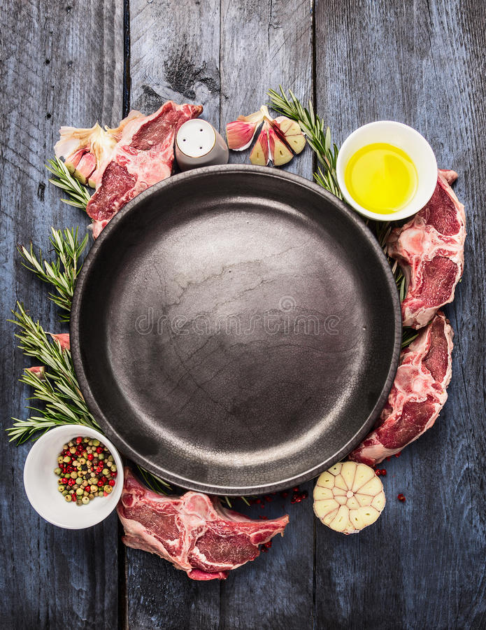 Empty plate with raw lamb loin chops meat , oil, herb and spices on blue wooden background. Top view royalty free stock image