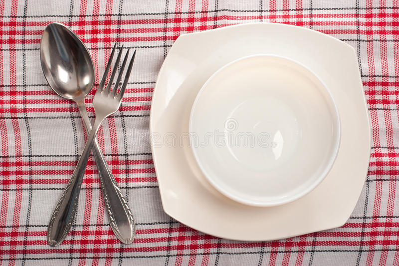 Empty plate, spoon and fork. On chequered tablecloth royalty free stock photos