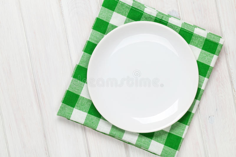 Empty plate and towel over wooden table background royalty free stock photography