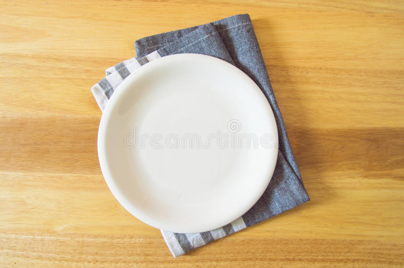 Empty plate and towel over wooden table background royalty free stock photo