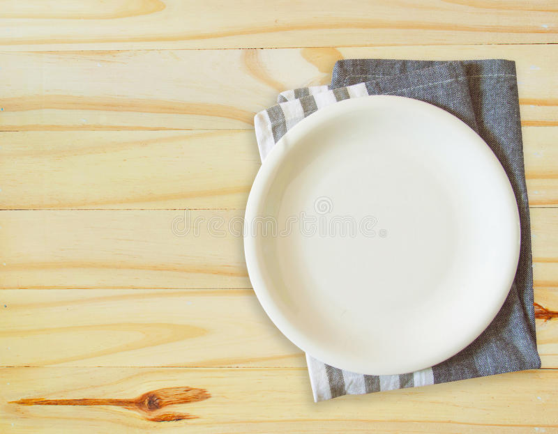 Empty plate and towel over wooden table background royalty free stock images