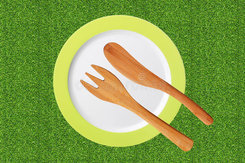Empty plate and wooden fork and knife on green grass stock photos