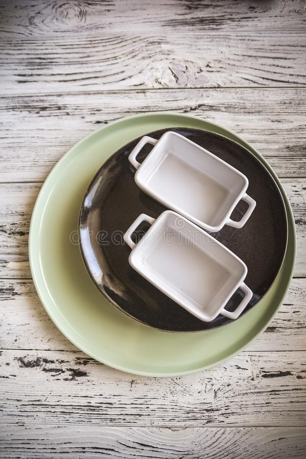 Empty plates and dishes for baking on a white wooden table closeup and copy space royalty free stock image