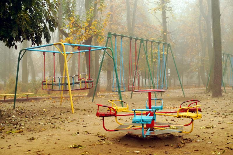 Empty playground with carousels and swings in misty park stock photo