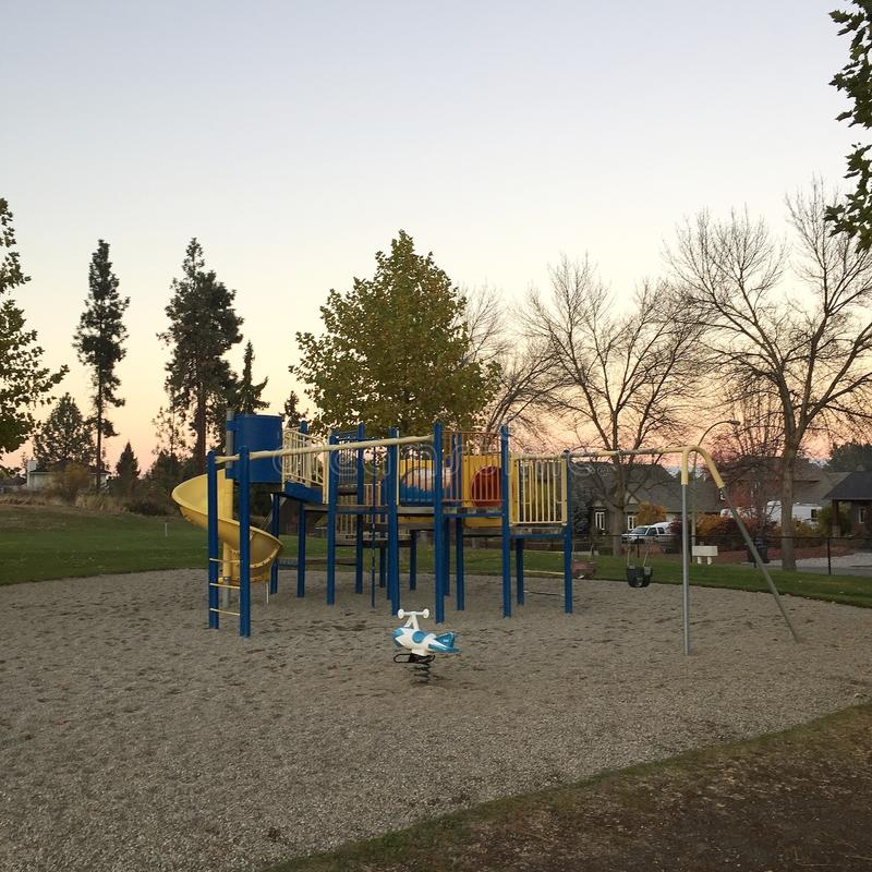 Empty playground at sunset. Empty playground in autumn at sunset. Bare trees and tall pine trees with house and clear orange and grey blue sky in background royalty free stock image