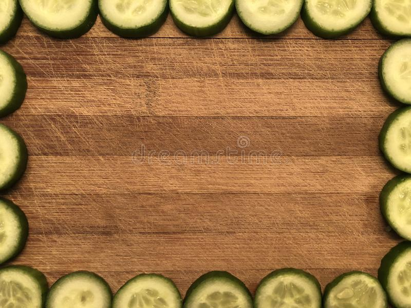 Empty postcard or frame with slides cucumbers, note paper on wooden background stock photo