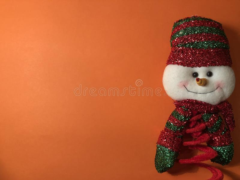 Empty postcard with snowman figure, note paper on orange background stock photos