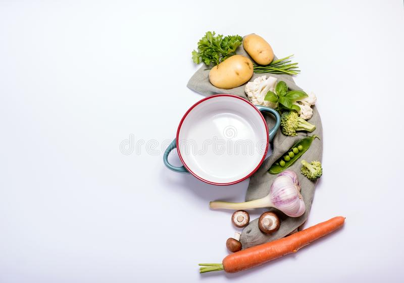 Empty pot with vegetables around it for healthy vegan cooking, soup or stew ingredients, cooking concept over white background. Place for text stock images