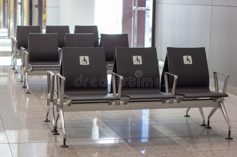 Empty priority public seats for disabled people. White sign with a handicap man in a wheelchair. Empty priority public seats for disabled people. White sign royalty free stock photography