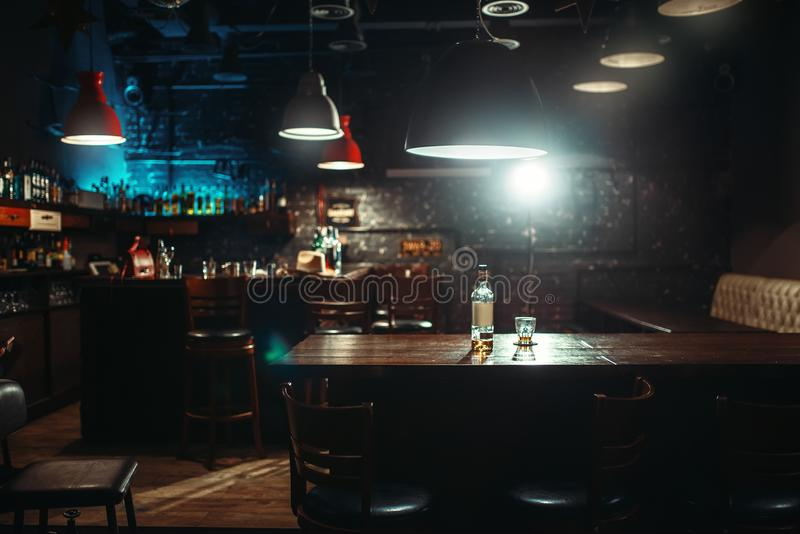 Pub, bottle of alcohol and glass on bar counter. Empty pub, bottle of alcohol and glass on bar counter. Restaurant interior, nobody stock photography