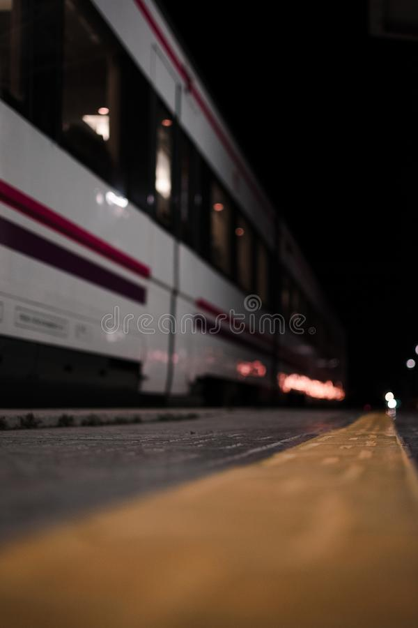 Empty rail road station at night. The train is going on the tracks. Empty rail road station at night. The wagons of the white train is going on the tracks royalty free stock photography