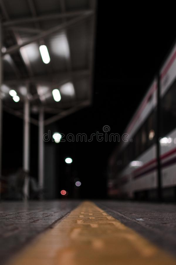 Empty rail road station at night. The train is going on the tracks. Empty rail road station at night. The wagons of the white train is going on the tracks stock photography