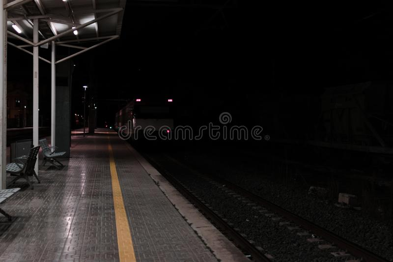Empty rail road station at night. The train is going on the tracks. Empty rail road station at night. The wagons of the white train is going on the tracks stock photos