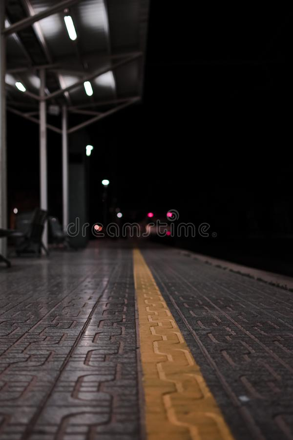 Empty rail road station at night. The train is going on the tracks. Empty rail road station at night. The wagons of the white train is going on the tracks royalty free stock image