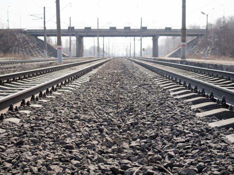 Empty railway lines, rails, sleepers, rubble and transport bridge afar, close up, wide angle, toned brown, selective. Focus. Urban, industry, transportation stock images