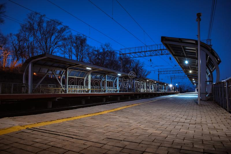 Empty railway station at dusk. Railway station without people and without trains in the dark. The platform is empty royalty free stock photos