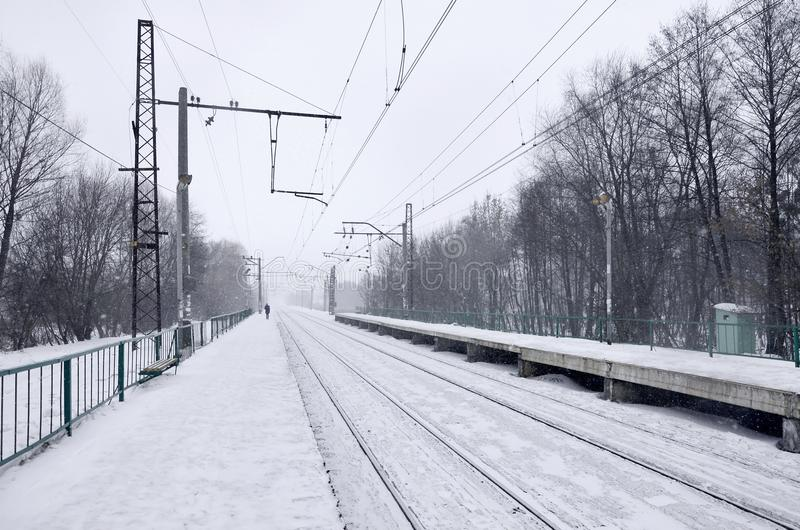 Empty railway station in heavy snowfall with thick fog. Railway rails go away in a white fog of snow. The concept of the railway. Transport in winter royalty free stock photography