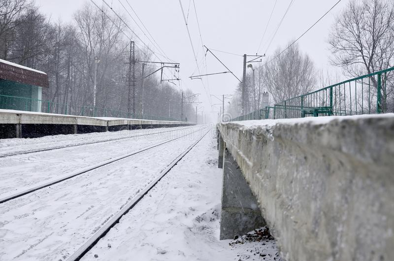 Empty railway station in heavy snowfall with thick fog. Railway rails go away in a white fog of snow. The concept of the railway. Transport in winter royalty free stock image
