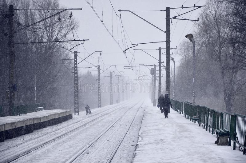 Empty railway station in heavy snowfall with thick fog. Railway rails go away in a white fog of snow. The concept of the railway. Transport in winter royalty free stock photos