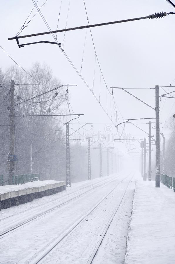 Empty railway station in heavy snowfall with thick fog. Railway rails go away in a white fog of snow. The concept of the railway. Transport in winter stock photo