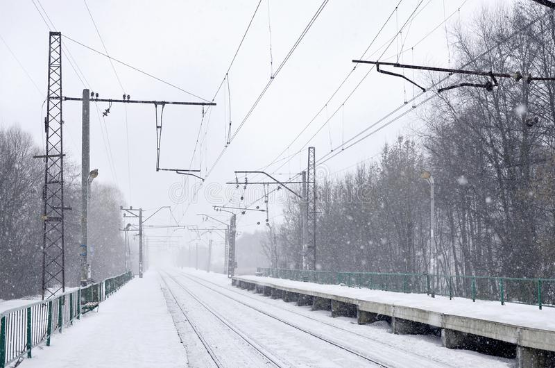 Empty railway station in heavy snowfall with thick fog. Railway rails go away in a white fog of snow. The concept of the railway. Transport in winter stock photos