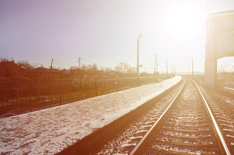 Empty railway station platform for waiting trains `Novoselovka` in Kharkiv, Ukraine. Railway platform in sunny winter da. Y royalty free stock photography