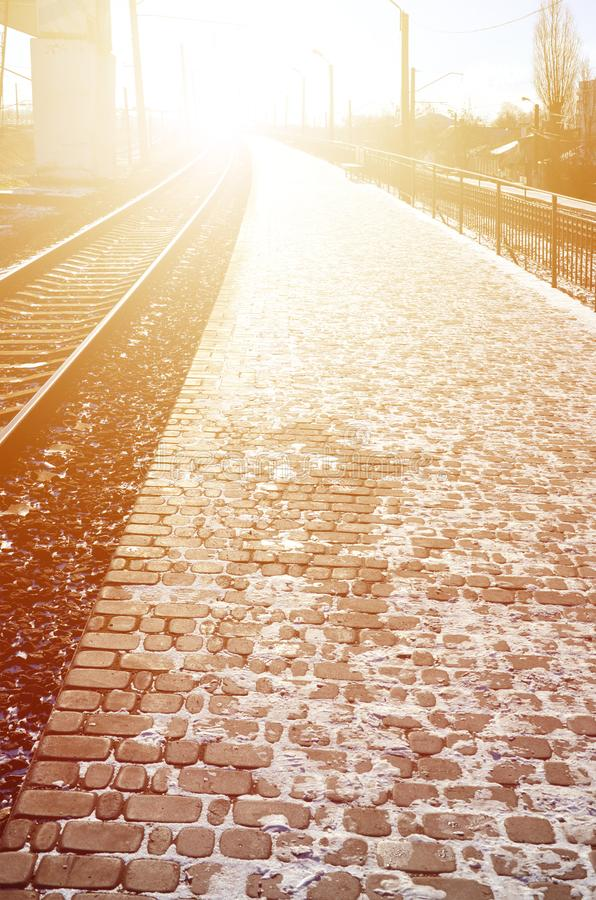 Empty railway station platform for waiting trains `Novoselovka` in Kharkiv, Ukraine. Railway platform in sunny winter da. Y stock photography