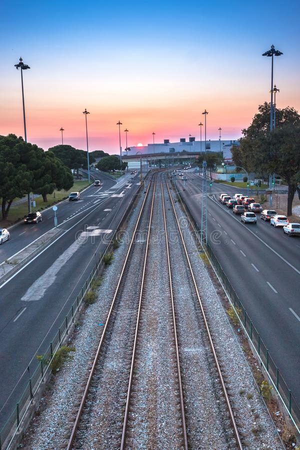 Empty Railway at Sunset. Image of empty railway and highway in Belem, Lisbon, Portugal at colorful sunset royalty free stock photos