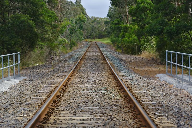 Empty railway surrounded with green trees. And pebbles on ground stock photography