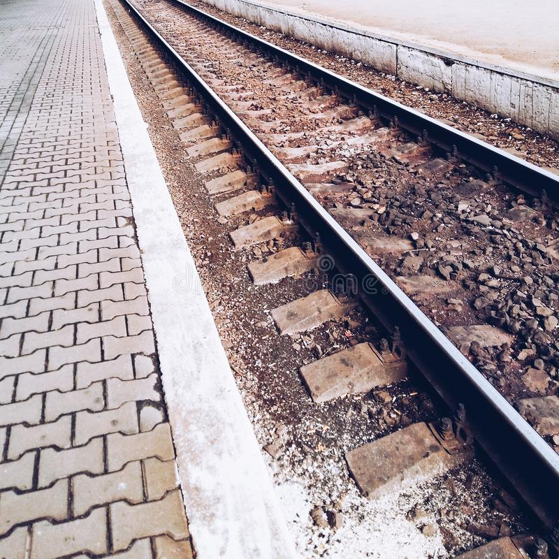 Empty railway track close-up. Railway station on a cloudy summer day. Free platform way stock photos