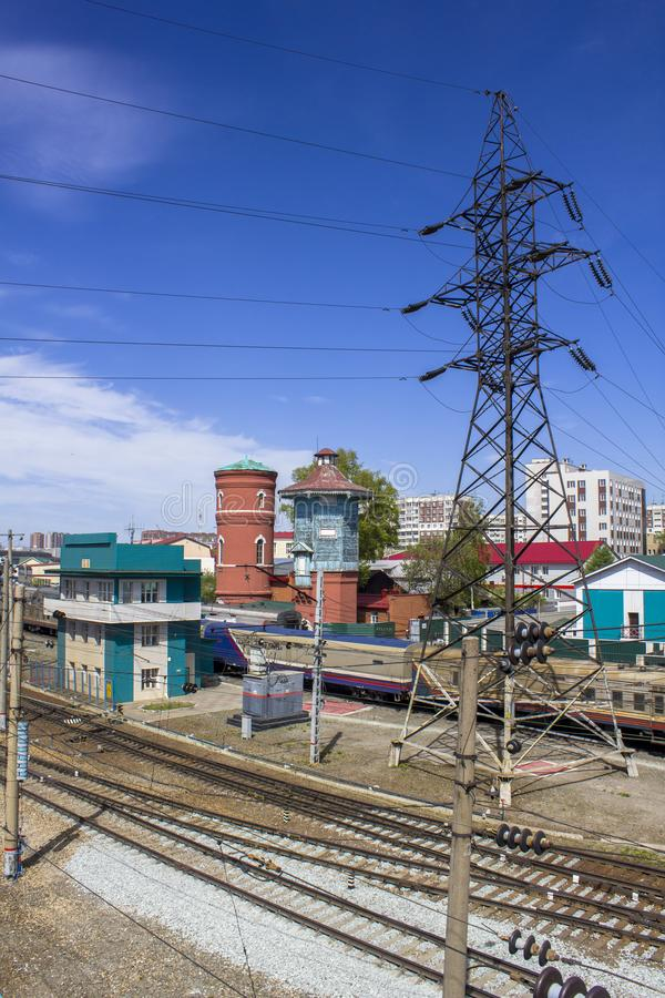 Empty railway tracks on the background of modern trains with cars, power lines, station buildings and the city. A empty railway tracks on the background of stock photos