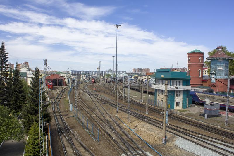 Empty railway tracks on the background of modern trains with cars and station buildings. A empty railway tracks on the background of modern trains with cars and royalty free stock image