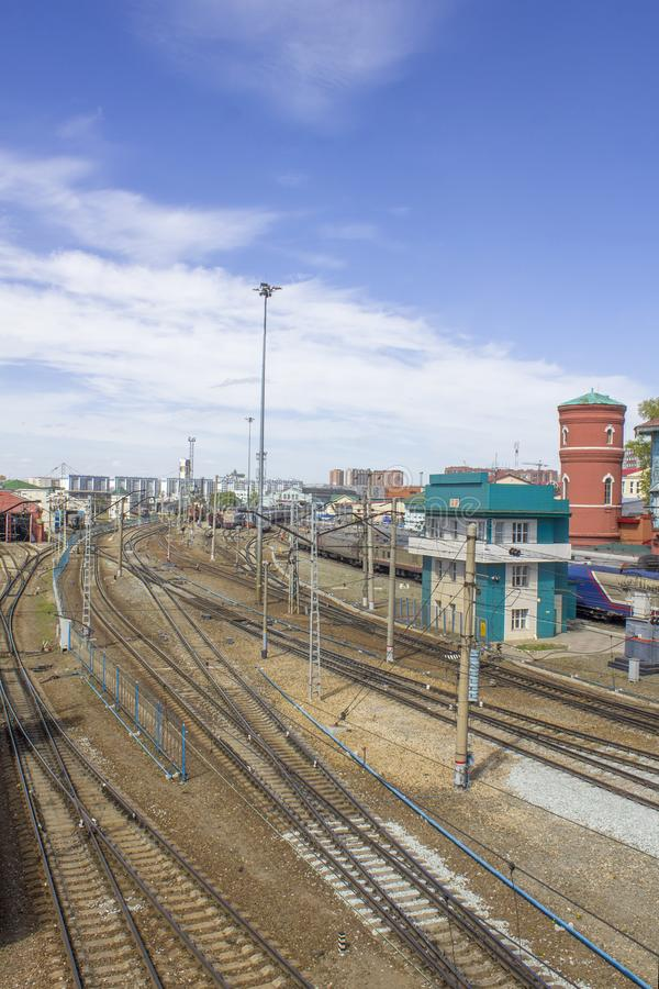 Empty railway tracks on the background of modern trains with cars, station buildings and the city. A empty railway tracks on the background of modern trains with stock photos