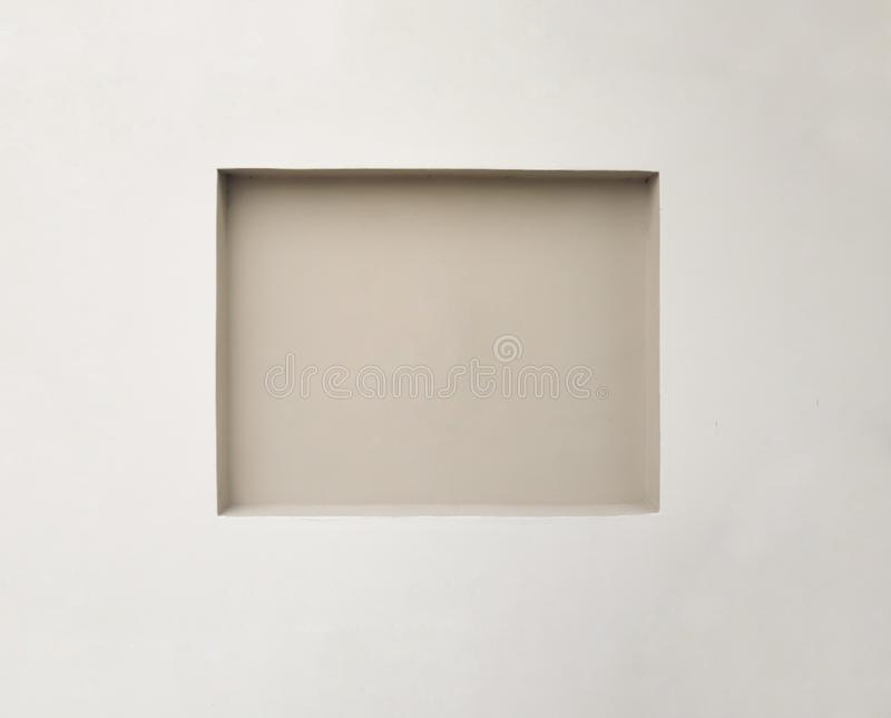Empty recessed square space in a wall, for displaying or hanging art. Center focus space indoors with copy space. Light brown or royalty free stock photos