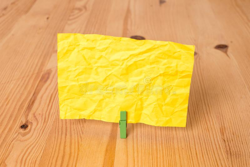 Empty rectangle square shaped reminder note in the centre of a wooden floor held by a green clothespin. Colored paper in. Empty reminder wooden floor background royalty free stock photos