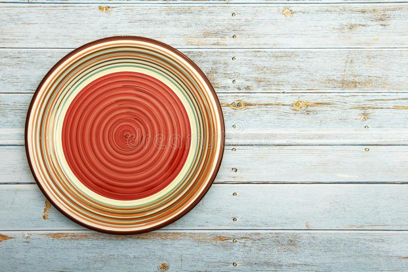 Empty red ceramic dish plate with spiral pattern on wooden white blue background. Top view with copy space. Empty red ceramic dish plate with spiral pattern on stock photography