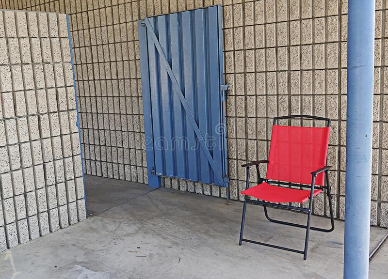 An Empty Red Chair Sets Outside An Open Blue Gate Hanging On White Brick Wall stock photography