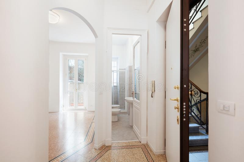 Empty renovated apartment entrance with security door. Bathroom and living room in Europe royalty free stock photos