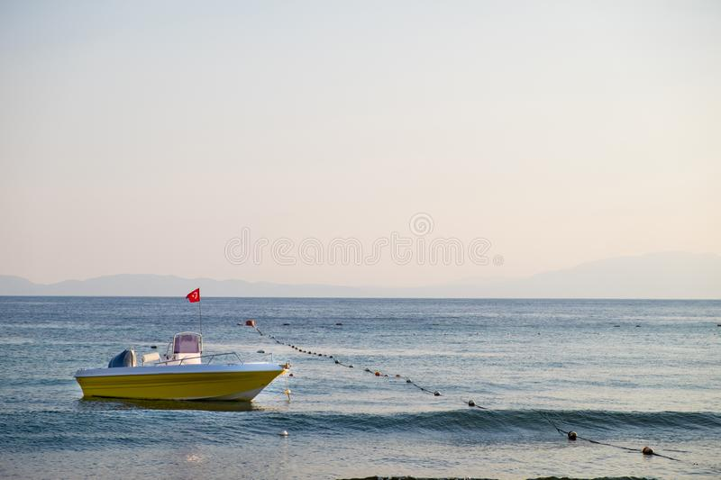 Empty rescue boat with the flag of Turkey to the sea on the background of the rocky coast under the blue sky. stock images