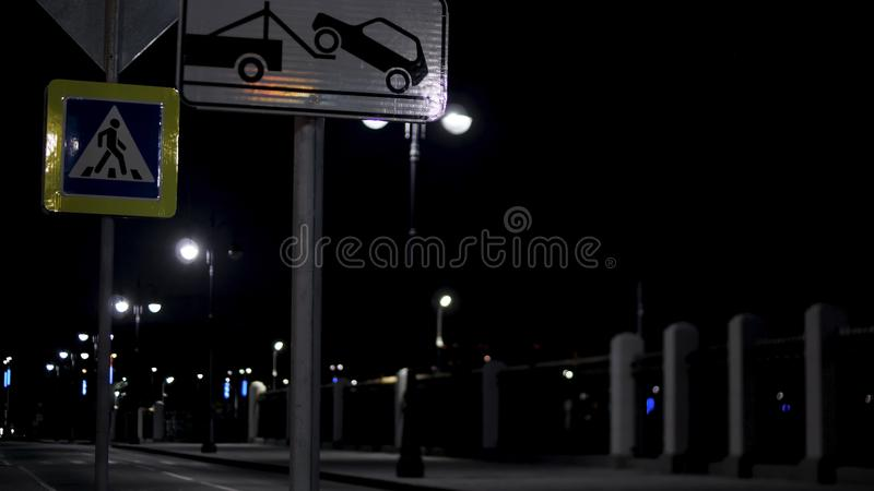 Empty residential street in the late evening with road signs and lanterns on black sky background. Stock footage. Night. Empty residential street in the late royalty free stock images
