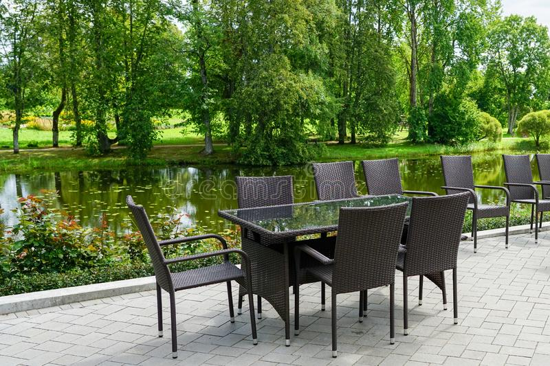 Empty restaurant with brown chairs by the beautiful pond in summer royalty free stock images