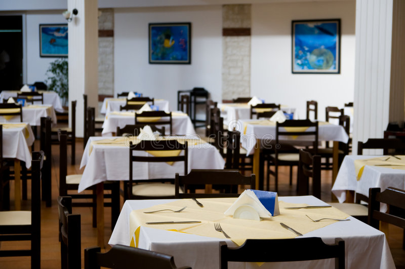 Empty Restaurant Tables. Interior of a modern restaurant with empty tables and chairs royalty free stock photos