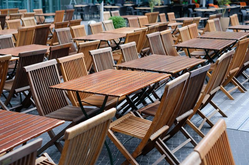Empty restaurant, empty tables and chairs in restaurant on day o. Empty restaurant - wooden chairs and tables outdoor stock image