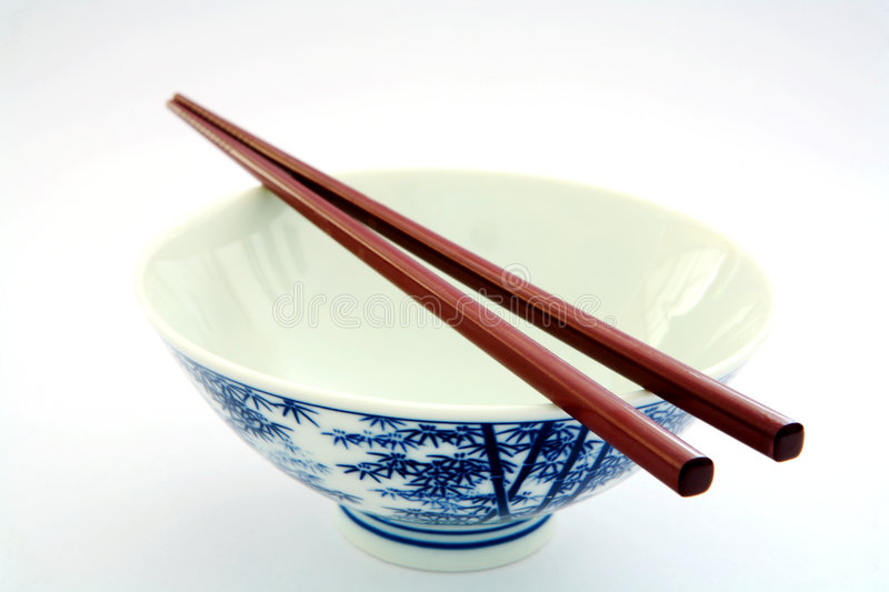 Empty rice bowl. Chopsticks lying in anticipation on top of an empty rice bowl royalty free stock photo
