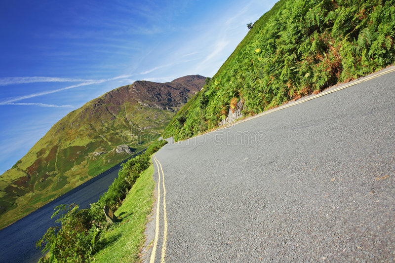 Empty road. Empty winding road next to lake with mountain backdrop royalty free stock images